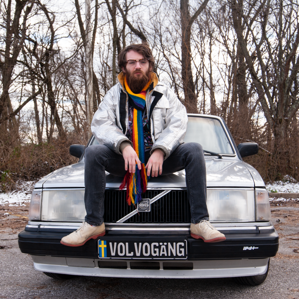 Andy sitting on hood of a Volvo